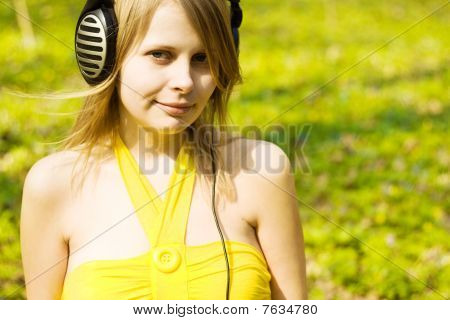 Blond girl listening music in headphones outdoors