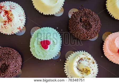 Assorted colorful cup cakes with colorful icing. Top view