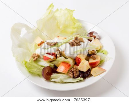 A traditional Waldorf Salad with lettuce, apple,grapes,walnuts,and celery sticks, topped with a modern  dressing of yoghurt with cream, salt, pepper and walnut oil.