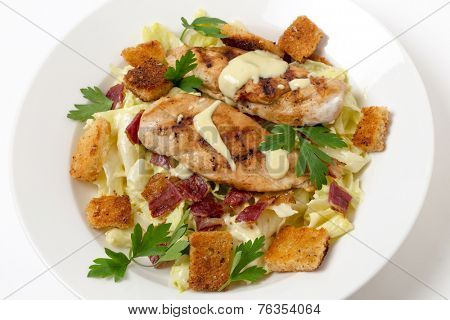 Chicken caesar salad, grilled chicken breast on a bed of lettuce tossed in a parmesan flavoured garnished with croutons, bacon bits and italian flat-leaf parsley.