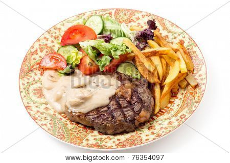 Grilled rib-eye beef steak served with mushroom sauce, salad and potato chips.