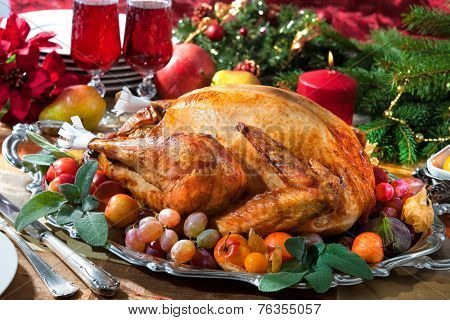 Roasted turkey on holiday table, candles and Christmas tree with ornaments