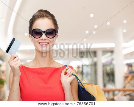 people, sale, christmas and holidays concept - smiling elegant woman in red dress with shopping bags and credit card over mall background