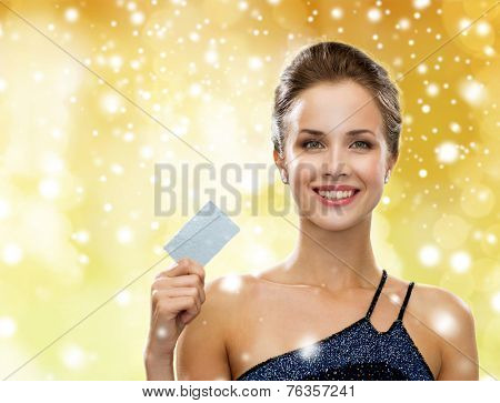 shopping, wealth, money, holidays and people concept - smiling woman in evening dress holding credit card over yellow lights and snow background