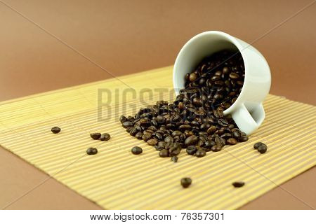 Coffee cup laying with coffee beans on placemat