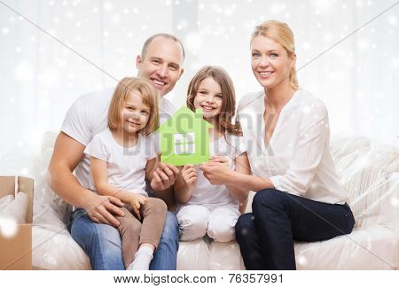 family, people, accommodation and ecology concept - smiling parents and two little girls moving into new home and waving hands over snowflakes background