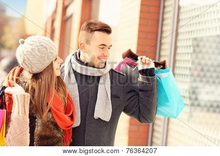 A picture of a beautiful couple shopping together in the city