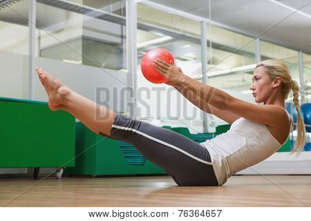 Side view of a sporty young woman in boat pose at fitness studio