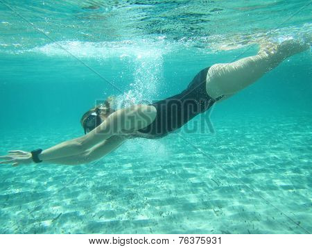 Female Swimmer Diving Underwater In Ocean