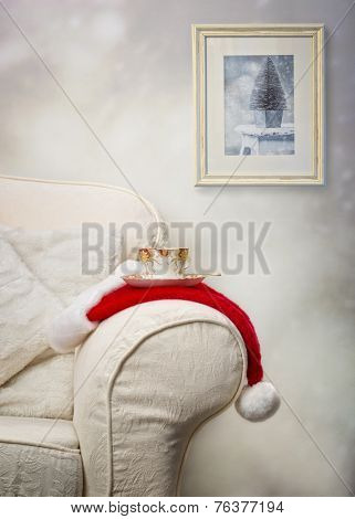 Cup of tea on santa hat with Christmas picture hanging in the background