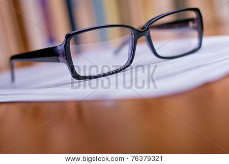 Close Up Eyeglasses On Top Of White Papers