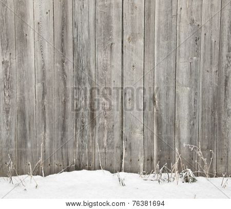 Frozen old wooden fence in snow