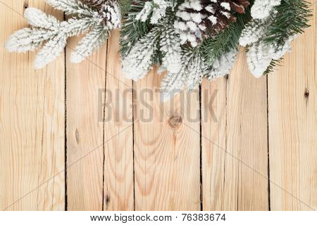 Christmas fir tree covered with snow on wooden board background with copy space