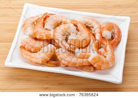 Cooked shrimps plate. On bamboo wooden table