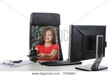 Little Girl With A Cup Of Coffee At A Table In Front Of A Computer