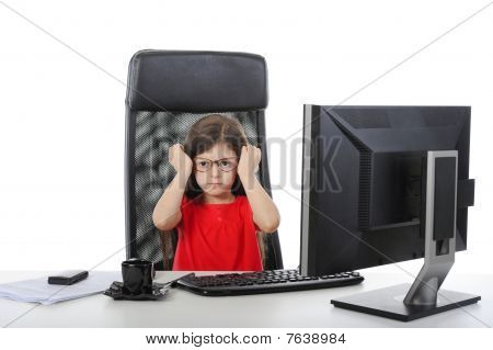 Little Girl Wears Glasses At The Table In Front Of A Computer