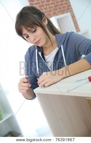 Single young woman assembling pieces of new furniture