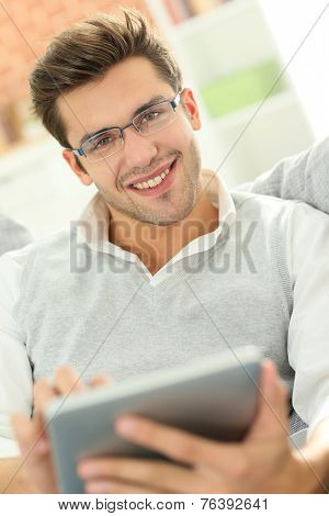 Young man websurfing with tablet, sitting in sofa