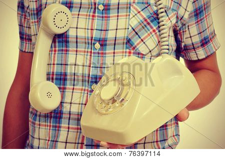 a young man with a rotary dial telephone in his hand, with a retro effect
