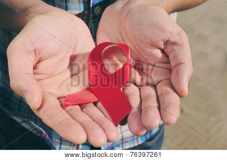 young man with a red awareness ribbon for the fight against AIDS in his hands, with a filter effect