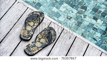 Pair of colorful floral slip slops or thongs left on a wooden deck above a pool at a tropical resort