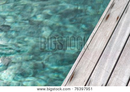 Close up of the boards of a wooden deck at the edge of a pool of mottled clear blue-green water in a conceptual background image
