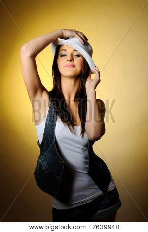 Young Sexy Model In Jeans And White Hat. Yellow Background