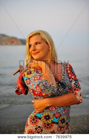 Young Pretty Woman Enjoing The Evening On The Beach Holding Her Shoes