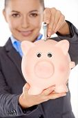 picture of insert  - Happy woman wearing formal jacket while inserting a folded banknote into a piggy bank  concept of saving money and profit - JPG