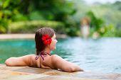 stock photo of infinity pool  - Beautiful woman relaxing in infinity swimming pool - JPG