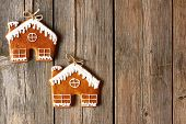 stock photo of gingerbread house  - Christmas homemade gingerbread house cookies over wooden background - JPG