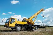 foto of boom-truck  - yellow automobile crane with risen telescopic boom outdoors over blue sky - JPG