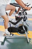 stock photo of exercise bike  - Fit people working out on the exercise bikes at the gym - JPG
