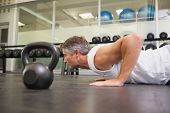 image of kettlebell  - Fit man using kettlebells in his workout at the gym - JPG