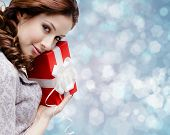 stock photo of gift wrapped  - Young woman is satisfied with a birthday gift wrapped in red paper - JPG