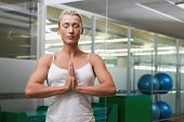 stock photo of joining hands  - Sporty young woman with joined hands and eyes closed at fitness studio - JPG