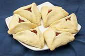 foto of purim  - apricot hamantaschen cookies  on a plate against blue tablecloth  - JPG