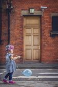 image of streetwalkers  - Little girl walking with her baloon on the London street  - JPG