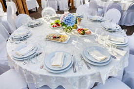 picture of banquet  - Elegant banquet tables prepared for a conference or a party and covered with a white tablecloth and decorated with flowers for guests - JPG