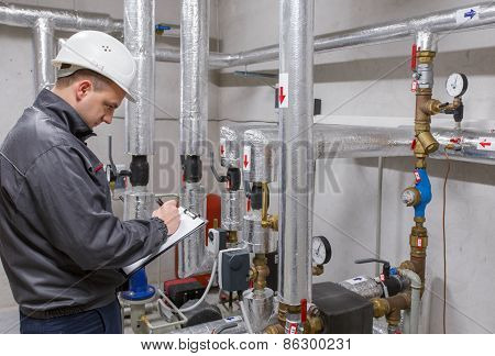 Technician inspecting heating system in boiler room