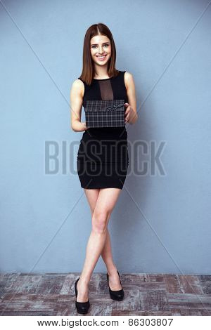 Full length portrait of a smiling woman holding gift