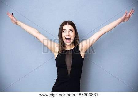 Cheerful young woman greeting you over gray background