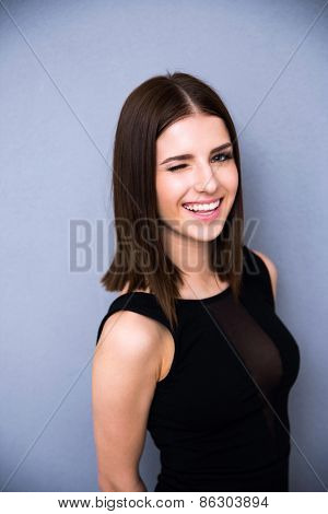 Portrait of attractive cute woman winking over gray background. Wearing sexy black dress. Looking at the camera
