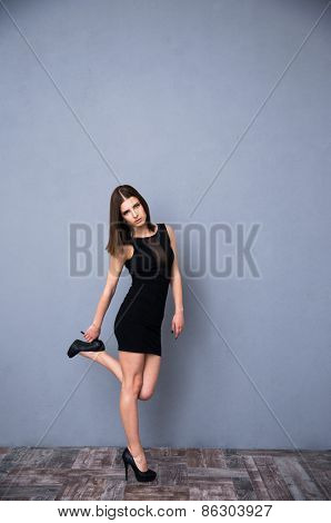 Full length portrait of a serious young woman in trendy black dress. Posing over gray wall. Looking at camera.