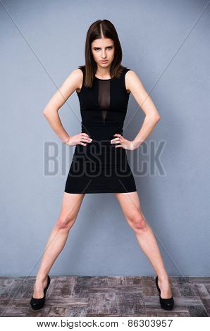 Full length portrait of a cute beautiful woman in vogue black dress posing at studio. Looking at camera. Over gray background