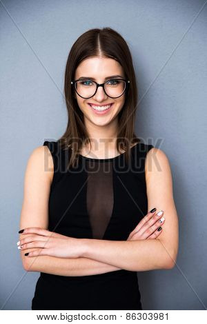 Portrait of a happy woman with arms folded and glasses standing over gray background. Wearing in fashion black dress. Looking at camera