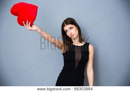 Beautiful young cute woman in sexy black dress holding red heart and looking on it. Over gray background.