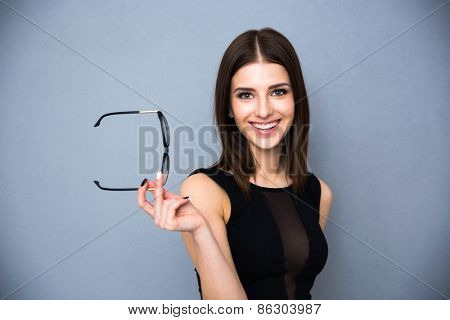 Portrait of a smiling cute woman holding glasses over gray background. Wearing black sexy dress. Looking at the camera.