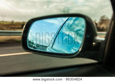 Car On The Road And Rear View Mirror