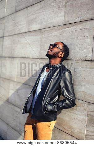 Outdoor Fashion Portrait Of Stylish Handsome African Man Relaxing In The City Against A Gray Wall